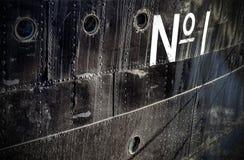 Foto av ett tecken för nummer ett på en grungy skeppsida Arkivfoton