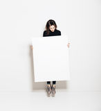 Foto av flickabanhoppningen i modernt galleri och att se den tomma vita kanfasen Horisontal modell arkivbilder