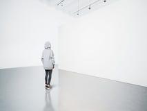 Foto av flickan i det moderna gallerit som ser den tomma kanfasen Arkivfoton