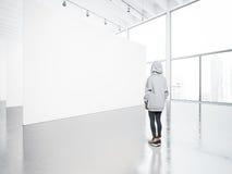 Foto av flickan i det moderna gallerit som ser den tomma kanfasen Fotografering för Bildbyråer