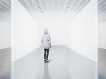 Foto av flickan i det tomma moderna gallerit som ser den tomma kanfasen Royaltyfri Fotografi