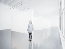Foto av flickan i det tomma moderna gallerit som ser den tomma vita kanfasen Stora fönster, strålkastare, konkret golv Fotografering för Bildbyråer