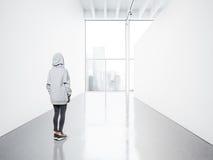 Foto av flickan i det tomma moderna gallerit som ser den tomma vita kanfasen Stora fönster, strålkastare, konkret golv Arkivfoto