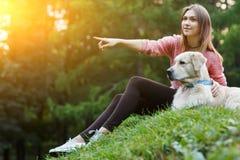 Foto av flickan som framåtriktat pekar bredvid hund på grön gräsmatta Royaltyfri Bild
