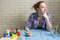 Foto av flickan som teckningsakrylmålarfärger på blå kläder Royaltyfri Foto
