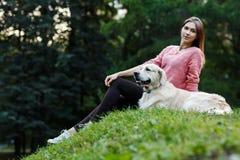 Foto av flickasammanträde med hunden på grön gräsmatta i sommardag Royaltyfria Foton