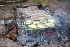 Foto av gallret för grillfest med grönsaker och korvar på brand i skog Royaltyfria Foton