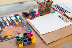 Foto av gouachen och vattenfärgen med borsteuppsättningen i konststudio Olje- målarfärger suddiga på paletten arkivfoto