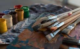 Foto av gouachen och vattenfärgen med borsteuppsättningen i konststudio Olje- målarfärger suddiga på paletten arkivbilder