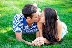 Foto av gulliga par som kysser och ligger på gräset i fältet Royaltyfria Foton