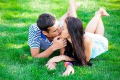 Foto av gulliga par som kysser och ligger på gräset i fältet Arkivfoto