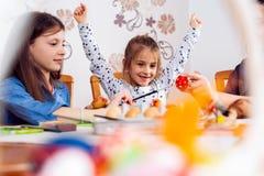 Foto av gulliga ungar som målar påskägg royaltyfri fotografi