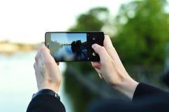 Foto av händer för man` som ett s rymmer telefonen och tar fotoet av en flod Arkivfoto