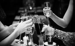 Foto av hållande exponeringsglas för folk av vin och att klirra royaltyfria bilder