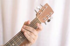 Foto av handen för man` som s spelar den akustiska gitarren, närbild fotografering för bildbyråer