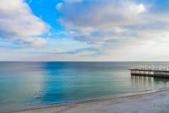 Foto av havet och den molniga himlen I vattnet är konstruktionen av pir, som leder till den sandiga kusten arkivbilder