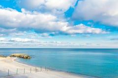 Foto av havet och den molniga himlen På kusten i vattnet är enorma stenar och restna av en konkret struktur arkivfoto