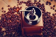 Foto av kaffekvarnen och grillade bönor på den underbara bruntet Royaltyfria Bilder