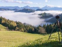 Foto av kameran på en tripod som tar foto av det härliga soluppgånglandskapet av helgonet Thomas Church i Slovenien på bergstoppe fotografering för bildbyråer