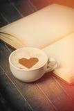 Foto av koppen kaffe och den öppnade förskriftsboken på det underbara krönet Arkivfoton