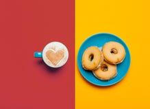 Foto av koppen kaffe och kakor på det underbara färgrikt Arkivfoton