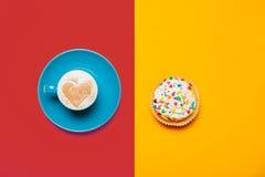Foto av koppen kaffe och muffin på det underbara färgrikt Royaltyfria Bilder