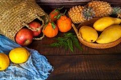 Foto av korgen som ?r fullt med l?ckra tropiska frukter p? tabellen arkivfoto