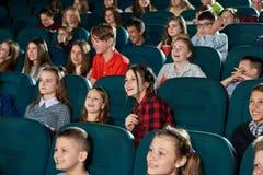 Foto av lyckliga barn som håller ögonen på film i bion och skratta Royaltyfri Foto
