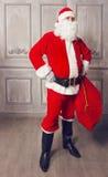 Foto av lyckliga Santa Claus med den stora påsen av gåvor Arkivfoto