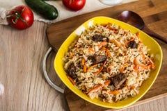 Foto av maträtten av uzbekpilaff som göras av ris och morötter, kött och lökar Arkivbild