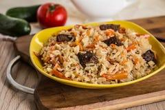 Foto av maträtten av uzbekpilaff som göras av ris och morötter, kött och lökar Royaltyfria Bilder