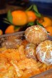 Foto av nya orange citruns som skalas och den delas upp Royaltyfri Fotografi