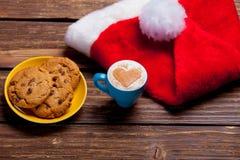 Foto av plattan mycket av kakor, den Santa Claus hatten och koppen av coffe Arkivbild