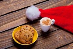 Foto av plattan mycket av kakor, den Santa Claus hatten och koppen av coffe Royaltyfri Bild