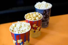 Foto av popcorn i koppar Popcorn n?ra bion H?lla ?gonen p? en film, en tecknad film med popcorn Bioperiod med popcorn royaltyfri fotografi