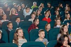 Foto av roliga barn som håller ögonen på film i bion Arkivfoton