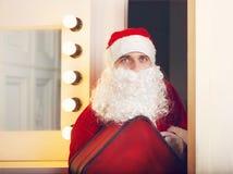 Foto av Santa Claus som ser kameran som kommer till dörren Royaltyfri Bild