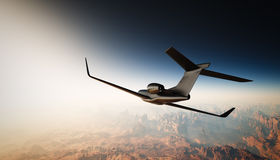 Foto av svarta Matte Luxury Generic Design Private Jet Flying i himmel under jordyttersidan bakgrundskanjontusen dollar Arkivfoto