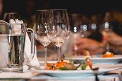 Foto av två tomma vinexponeringsglas på en tjänad som tabell i en restaurang Royaltyfria Bilder
