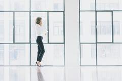 Foto bedrijfsvrouw die modern kostuum dragen, smartphone spreken en documenten in handen houden Het bureau van de open plekzolder Stock Foto's