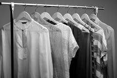Foto in bianco e nero dei vestiti delle donne sui ganci gabinetto del wo Fotografia Stock