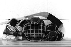 Foto in bianco e nero dell'ingranaggio dell'hockey del ` s del bambino: casco, bastone, guanti, pattini Fotografie Stock Libere da Diritti