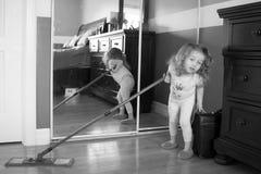Foto in bianco e nero di piccola ragazza bianca La ragazza sta contribuendo a pulire la casa Tiene una zazzera Immagini Stock