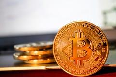 Foto Bitcoins de oro en el ordenador portátil concepto comercial de moneda crypto Foto de archivo libre de regalías