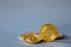 Foto Bitcoins de oro en fondo azul concepto comercial de moneda crypto Foto de archivo