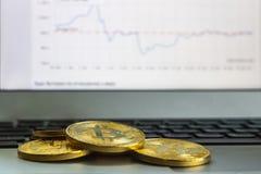 Foto Bitcoins de oro en fondo del ordenador portátil y del gráfico concepto comercial de moneda crypto Imagen de archivo libre de regalías