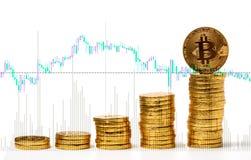 Foto Bitcoins de oro en fondo de la carta de las divisas Imagen de archivo