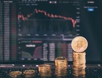 Foto Bitcoins de oro en fondo de la carta de las divisas Imagenes de archivo