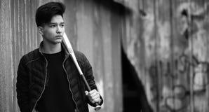 Foto blanca negra del hombre joven asiático al aire libre que presenta Foto de archivo