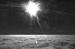Foto blanco y negro de HDR de un ala del aeroplano contra el cielo azul con las nubes debajo y el sol brillante del brigh adentro Imagenes de archivo